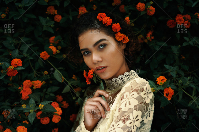 Attractive young woman in blouse and skirt near flower shrub