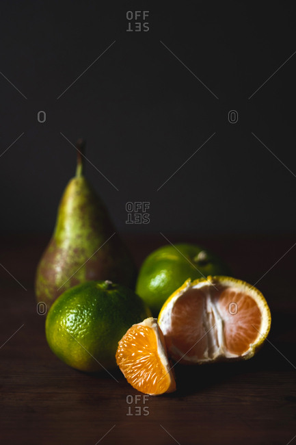 Tasty ripe peeled green tangerines and sweet pear on board on black background