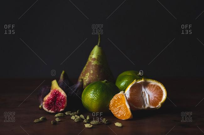 Tasty fresh peeled tangerines, fig, pear and nutmegs on board on black background