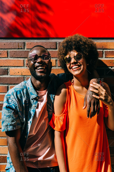 Attractive African-American man and woman in stylish outfits laughing and hugging while sitting near brick wall on street