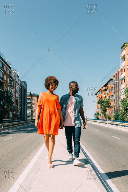 African-American couple in casual outfits holding hands together and walking along sidewalk between two roads in city
