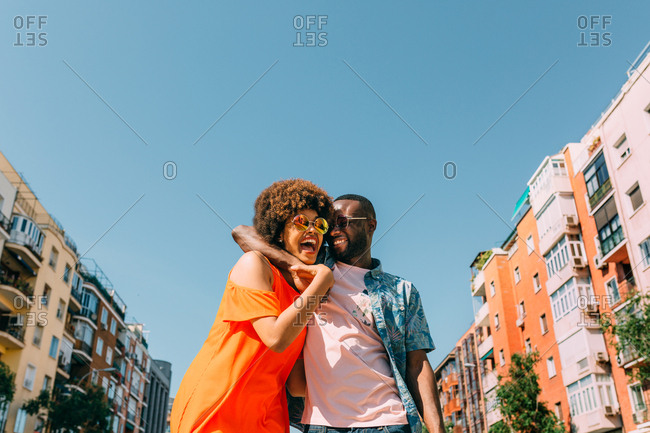 From below shot of African-American man and woman laughing and hugging while standing on background of buildings and clear blue sky