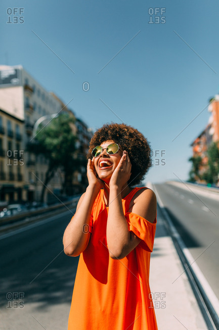 Lovely African-American woman in sunglasses cheerfully smiling and looking at clear blue sky while standing in middle of road in nice city