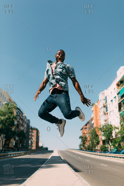 Handsome African-American man in casual outfit jumping and shouting over road in nice city on sunny day