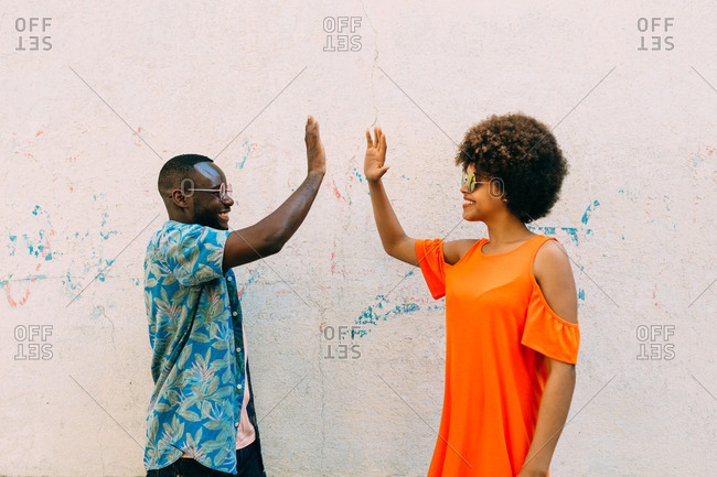 Black couple near cement wall with hands high five