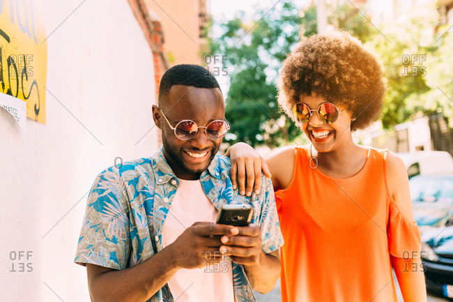 Funny African-American man and woman laughing and browsing modern smartphone while walking on street on sunny day