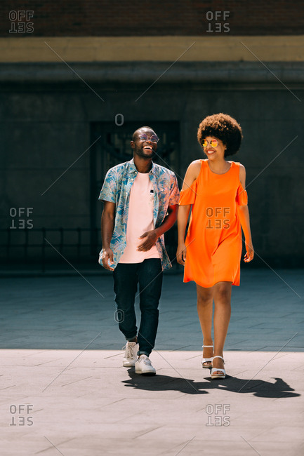 Stylish African-American man and woman laughing and walking on city street together on sunny day
