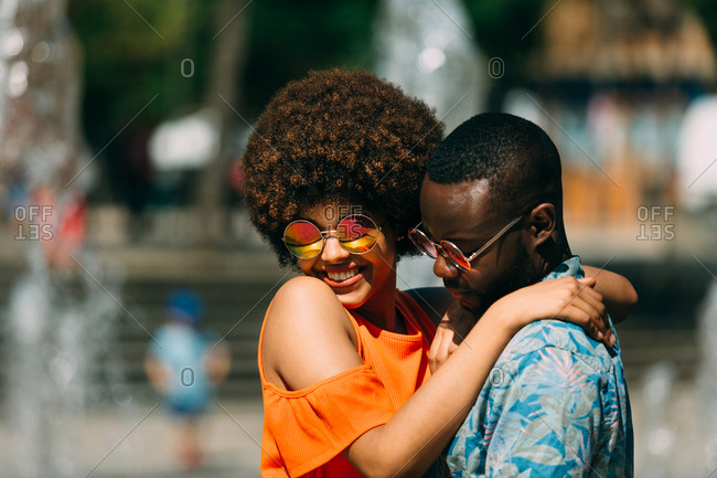 Handsome African-American man hugging pretty woman and laughing while standing near fountain together