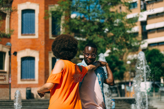 African-American man and woman smiling and dancing together on blurred background of fountain and street of sunny day