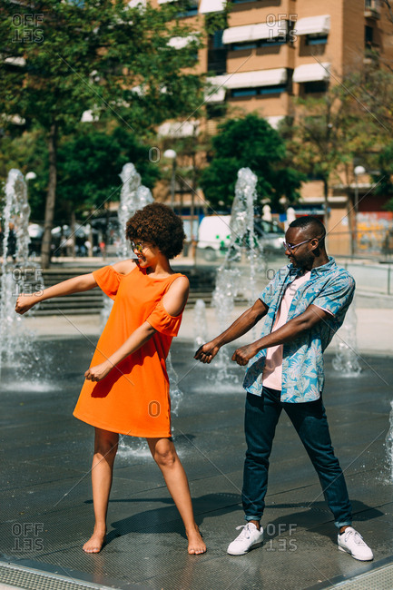 Attractive African-American man and barefoot woman standing near fountain on city street and performing swish swish funny dance moves together