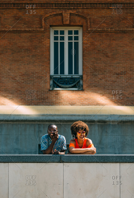 Smiling black couple leaning on border in city