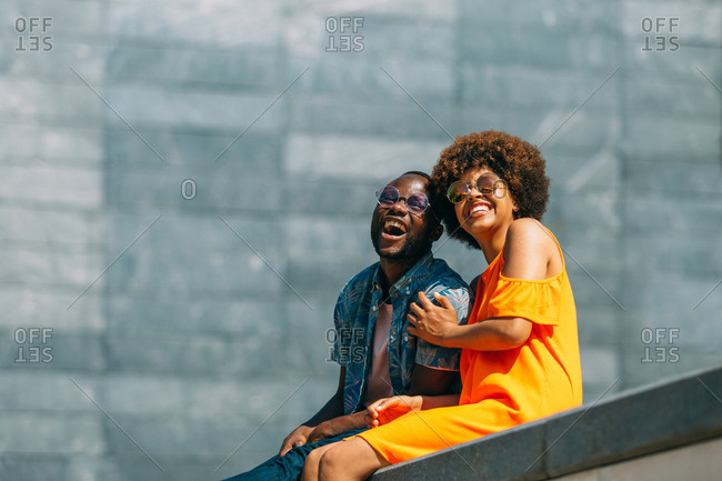 Attractive African-American man and woman laughing and leaning on each other while sitting on border on city street