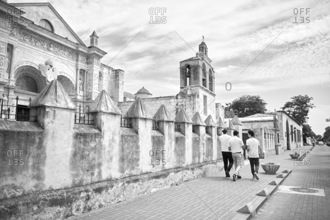 October 2, 2018: Photo of three friends walking near The Cathedral of Santa Mar�a la Menor in the Colonial Zone of Santo Domingo the capital of Dominican Republic. The oldest cathedral in the Americas. Fellows are shot from behind. The Cathedral is fronted with a golden-tinted coral limestone fa�ade, the church combines elements of both Gothic and Baroque with some lavish plateresque styles as exemplified by the high altar chiseled out of silver. There is also a treasury which has an excellent art collection of ancient woodcarvings, furnishings, funerary monuments, silver, and jewelry. Photo is taken in sunny autumn day with small clouds the sky. Photo is monochrome..