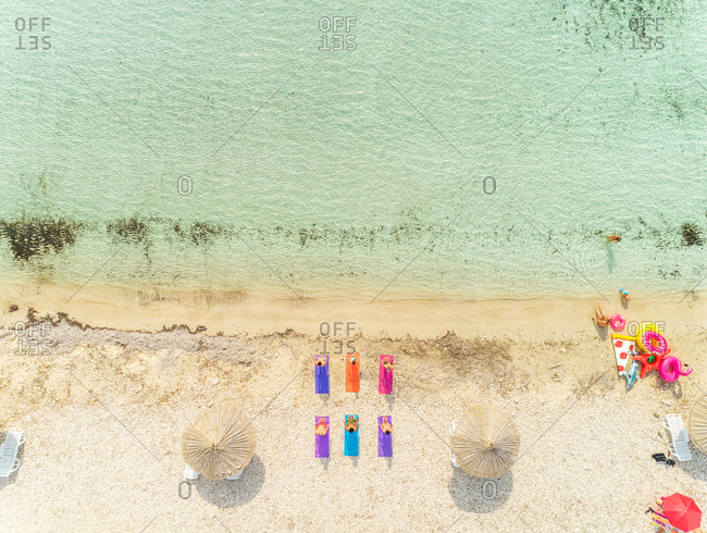 Aerial view of group of people doing yoga and children playing by inflatable colourful toys on beach.