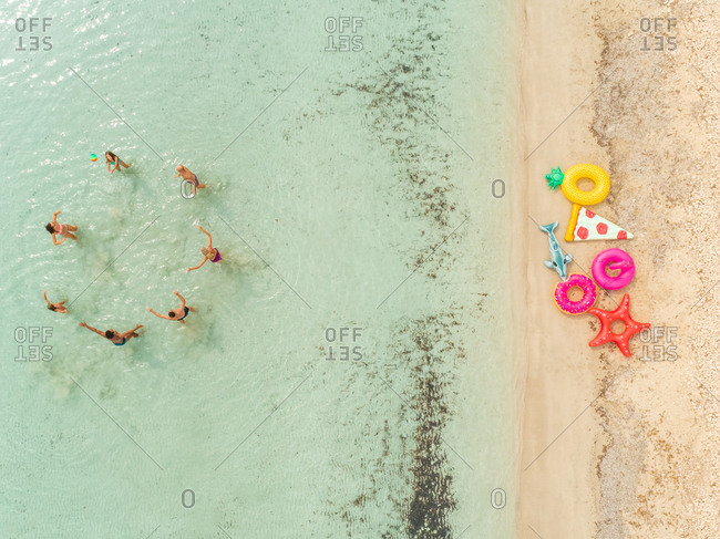 Aerial view of people playing ball standing in sea by sandy beach with inflatable matresses.