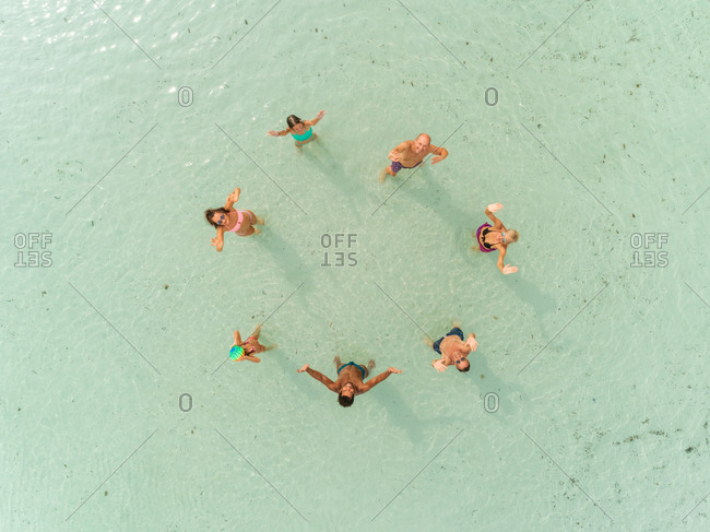 Aerial view of group of people in swimwear standing in sea playing volleyball.