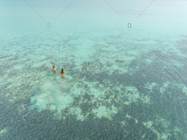 Aerial view of coral reef and man and woman walking into sea to dive.