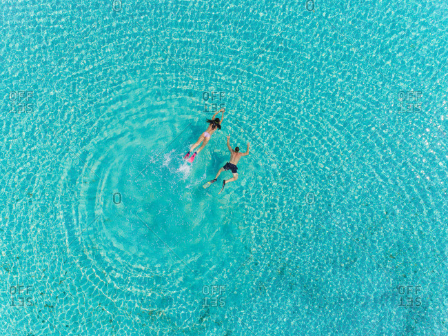 Aerial view of man and woman with masks and flippers diving in turquoise water.