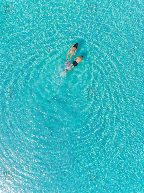 High aerial view of man and woman snorkeling next to each other in masks and flippers in transparent sea.