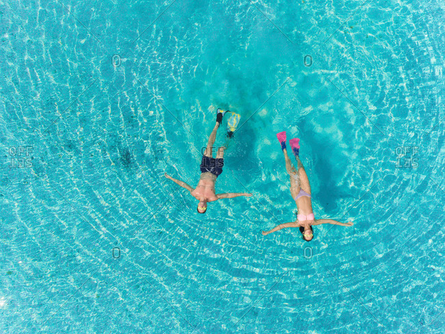 Aerial view of man and woman with masks and flippers swimming on their backs in clear sea.