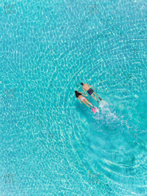 Aerial view of man and woman snorkeling holding hands in transparent sea.