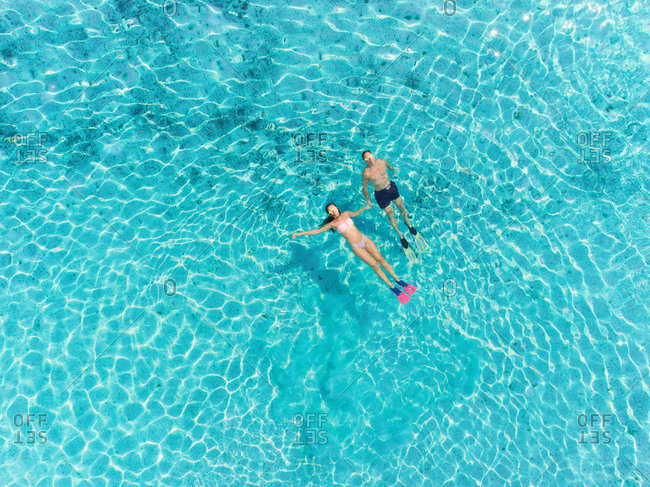 High aerial view of man and woman with masks and flippers relaxing on their backs in clear sea.