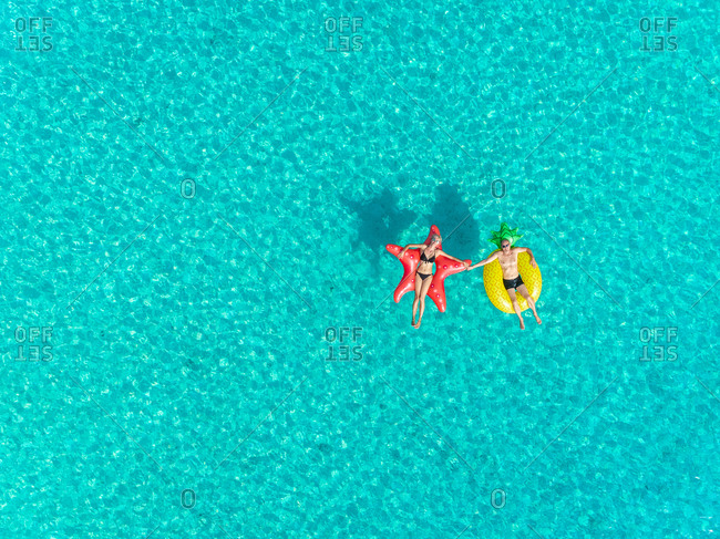 Aerial view of man and woman floating on inflatable star and pineapple shaped mattresses holding hands.