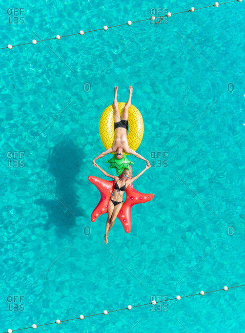 Aerial view of man and woman floating between string buoy on inflatable mattresses holding hands in clear sea.