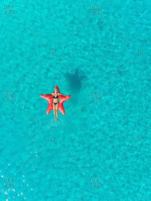Aerial view of one woman in bikini floating on inflatable star shaped mattress relaxing in clear sea.