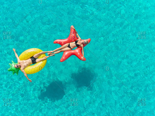 Close up aerial view of man and woman floating on inflatable mattresses touching each others feet in clear sea.