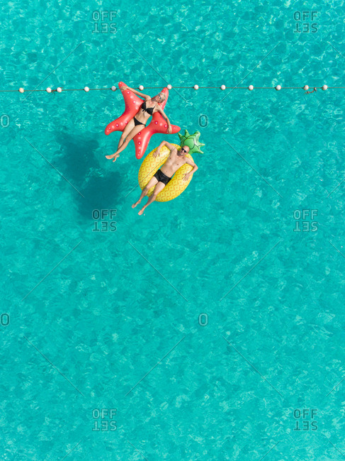 Aerial view of man and woman floating by string buoy on inflatable mattresses in clear sea.