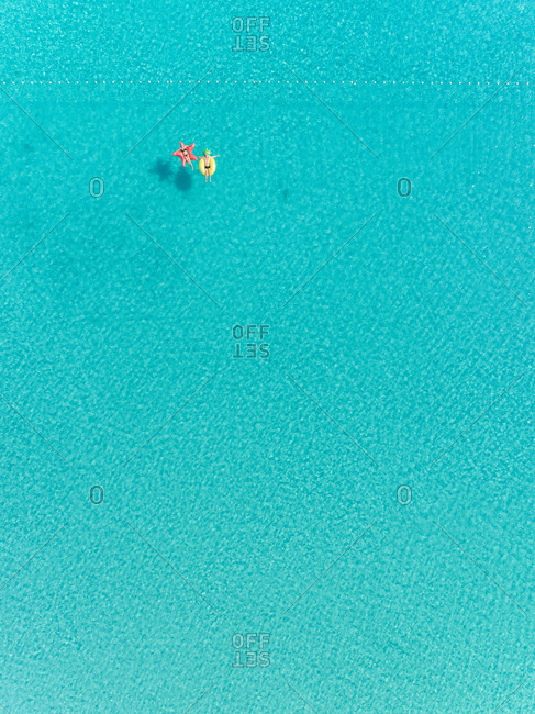 Aerial abstract view of two people floating in open sea on inflatables  in clear sea.