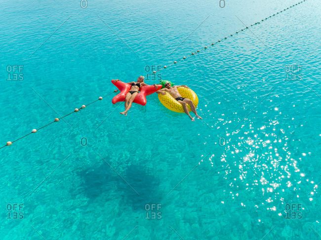 High view of couple floating by string buoy on inflatable mattresses in transparent blue sea.