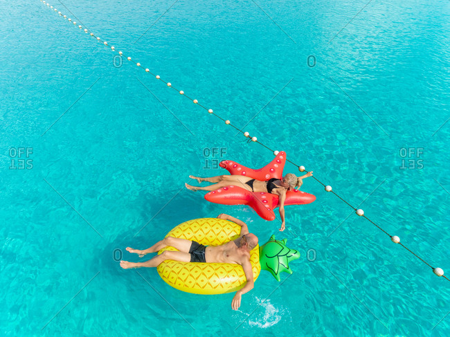 Close up aerial view of man and woman in bikini floating by string buoy on inflatable mattresses in clear turquoise sea.