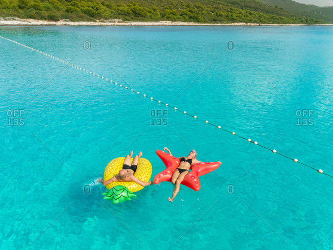 Aerial view of man and woman floating by string buoy on inflatable mattresses in clear blue Adriatic sea.