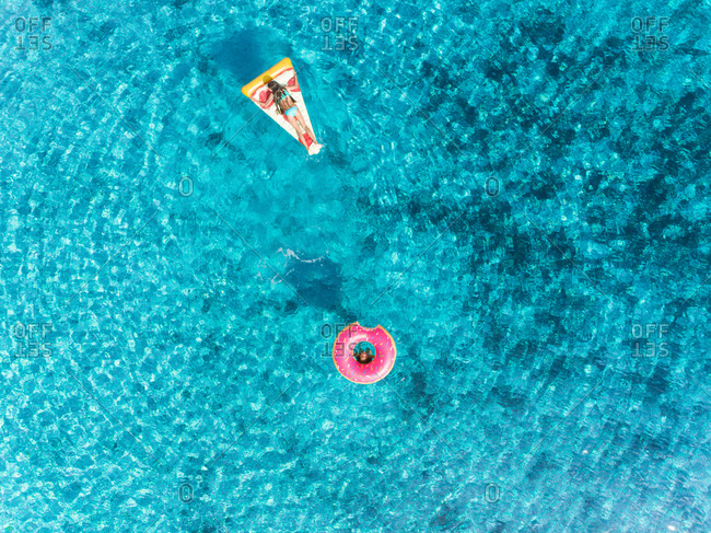 Aerial view of two young girls swimming and playing in sea with pizza and donut inflatables.