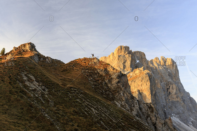 Hiker admires the peaks of Forcella De Furcia at sunrise. Funes Valley South Tyrol Dolomites Italy Europe
