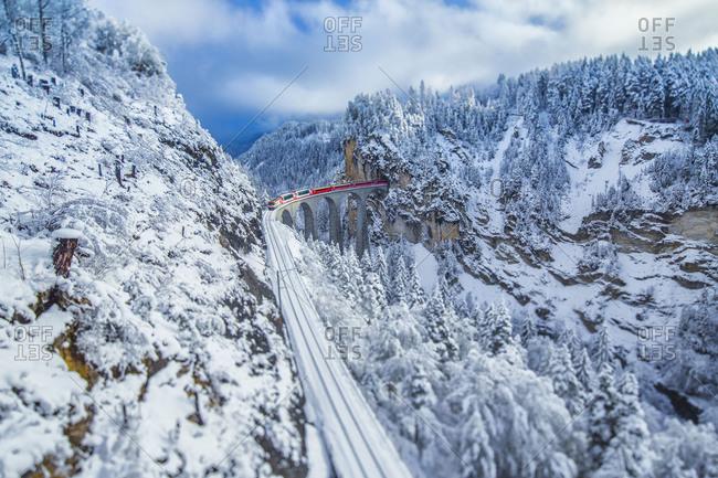 May 23, 2017: Bernina Express passes through the snowy woods around Filisur Canton of Grisons Switzerland Europe
