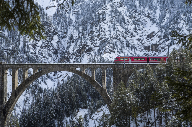 May 23, 2017: Bernina Express train on Wiesener Viadukt surrounded by snowy woods Davos Albula Valley Canton of Graubunden Switzerland Europe