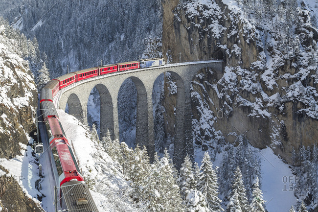 May 23, 2017: Bernina Express train on Landwasser Viadukt framed by snowy woods Filisur Albula Valley Canton of Graubunden Switzerland Europe