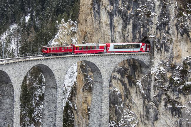 May 23, 2017: Bernina Express passes through Landwasser Viadukt and snowy woods Filisur Canton of Grisons Switzerland Europe