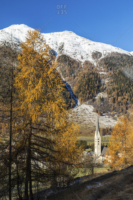 Autumn colors frame the village of Zernez surrounded by woods and snowy peaks Engadine Canton of Graubunden Switzerland Europe
