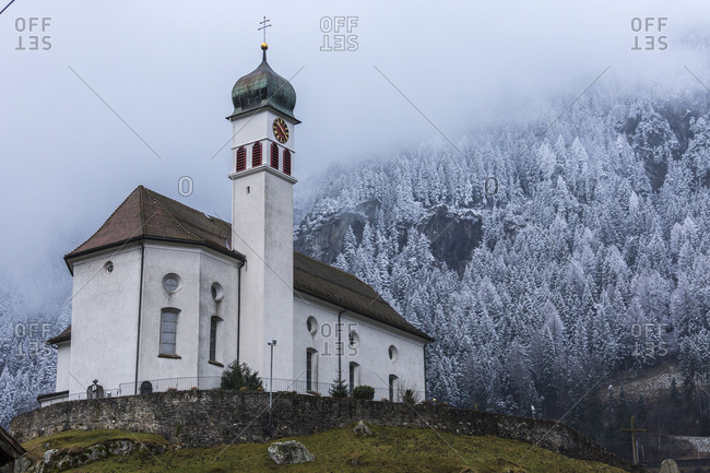 Clouds and mist on the alpine church of Wassen surrounded by snowy woods Canton of Uri Switzerland Europe