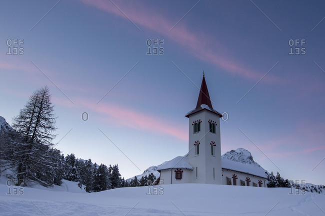 Pink sky at dawn on bell tower of the Chiesa Bianca surrounded by snow Maloja Engadine Canton of Graubunden Switzerland Europe