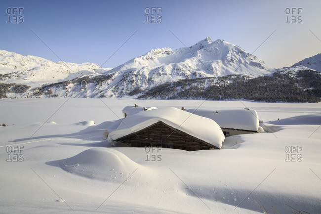 The alpine huts of Spluga covered with snow frame the Piz Da La Margna Maloja Engadine Canton of Graubunden Switzerland Europe