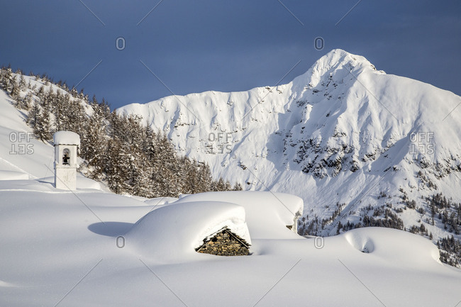 Bell tower and huts covered with snow framed by the high peaks Alpe Scima Chiavenna Valley Valtellina Lombardy Italy Europe