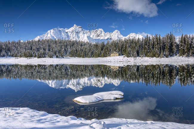 Wooden chalet surrounded by snowy peaks and woods reflected in Lake Palu Malenco Valley Valtellina Lombardy Italy Europe
