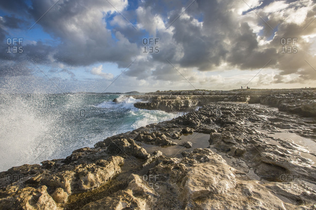 Sea waves crashing on the cliffs framed by clouds at sunset Devil's Bridge Antigua and Barbuda Leeward Islands West Indies