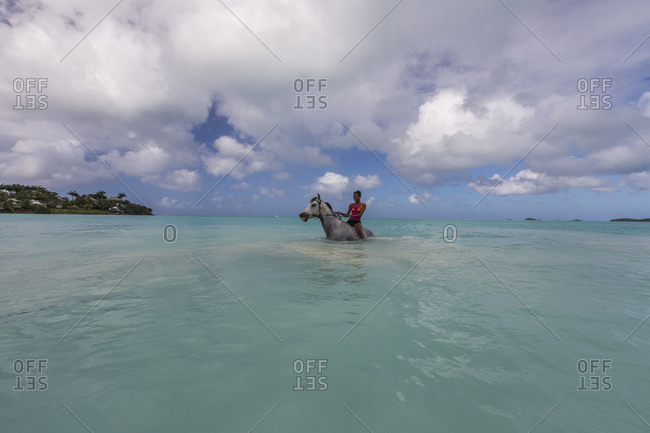 Girl on a horse in the turquoise caribbean sea Valley Church The Nest Antigua and Barbuda Leeward Islands West Indies