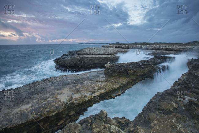 Sea waves crashing on the cliffs framed by sunset Devil's Bridge Antigua and Barbuda Leeward Islands West Indies
